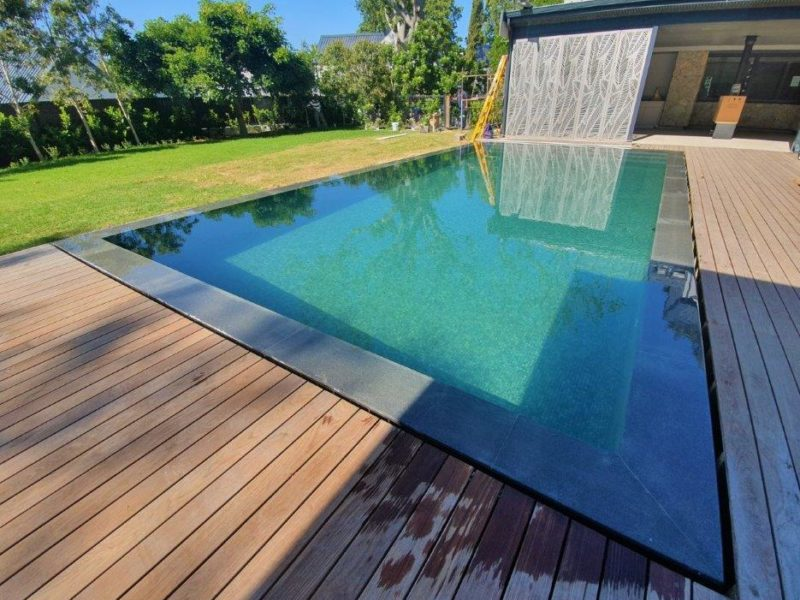 We created a narrow channel around the pool to carry the water to the rimflow reservoir, with this channel hidden by the decking. The decking was then brought right up to the tiled edge of the pool, leaving a 20mm gap for the water to flow into.