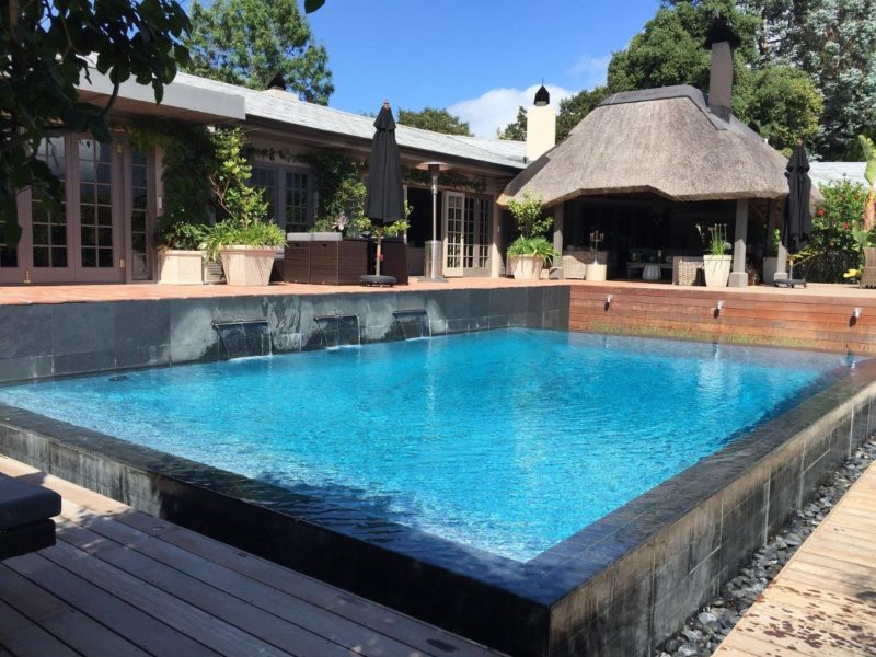 A stunning gunite rimflow pool. Quartz tiles and a Cemcrete Ocean Blue Poolcrete plaster make this pool stand out from the crowd.